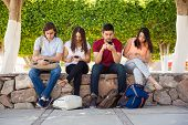 foto of ignorant  - Portrait of a group of college students ignoring each other and using their smartphones at school