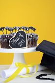 picture of graduation hat  - Happy Graduation Day party chocolate cupcakes with graduation cap hat topper decorations in yellow black and white party theme - JPG