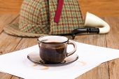 picture of private investigator  - Coffee cup paper sheets and detective hat on old Wooden table - JPG