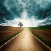 picture of symmetrical  - Lonely and moody road through empty fields with dramatic sky dark clouds interesting light and symmetrical composition - JPG