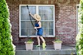 foto of spring-cleaning  - Housewife standing on a patio washing the windows of her house with a hose attachment as she spring - JPG