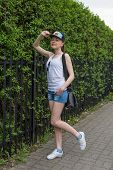 pic of stroll  - strolling girl in blue cap with green nature on background - JPG