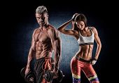 picture of pectorals  - young beautiful couple doing sport exercises with dumbbells - JPG