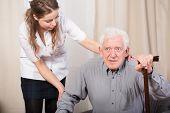 picture of older men  - Careful female caregiver helping older man to stand up - JPG
