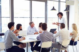 stock photo of coworkers  - Businesswoman presenting to colleagues at a meeting - JPG