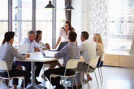foto of coworkers  - Businesswoman presenting to colleagues at a meeting - JPG
