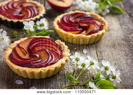 Tartlets With Plum On Wooden Background