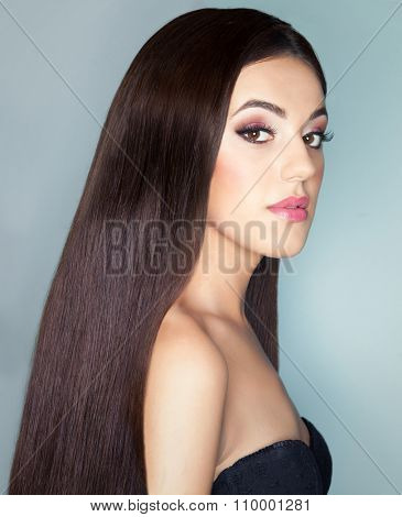 Young beautiful brunette woman with healthy long brown hair. Beauty haircare and hairdressing concept