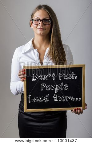 Don't Push People Lead Them… - Young Businesswoman Holding Chalkboard With Text