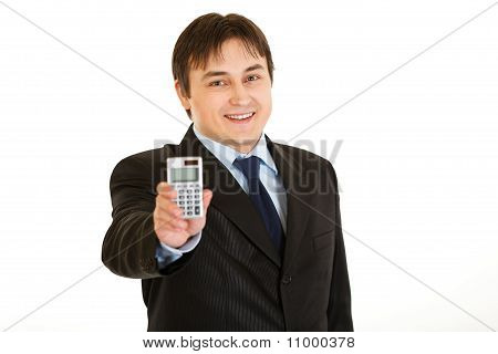 Smiling young businessman holding calculator in hand