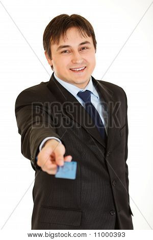 Smiling young businessman giving credit card