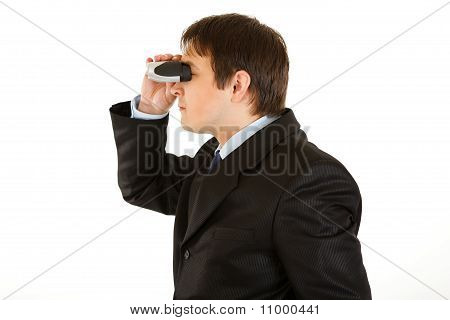 Interested young businessman looking through binoculars