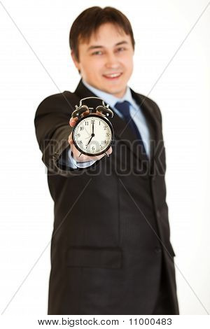 Smiling young businessman holding alarm clock in hand