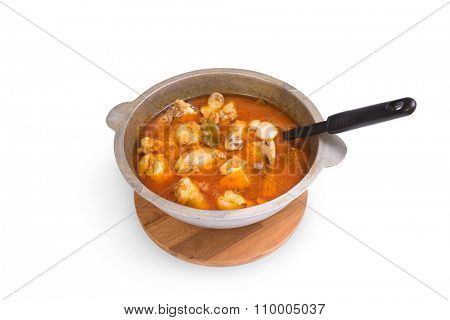 Stewed chicken in a metal pan. Isolated on white.