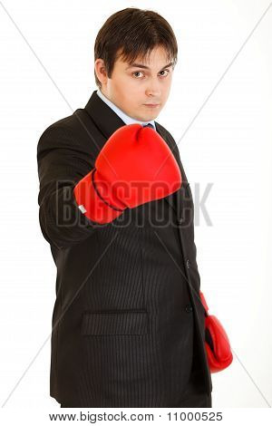 Confident young businessman with boxing gloves showing come on gesture