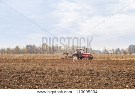 Red Tractor Plowing In Autumn