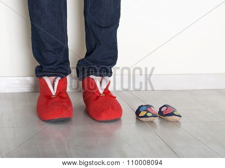 Family legs feet standing together, woman legs and small baby shoes on light background, conceptual