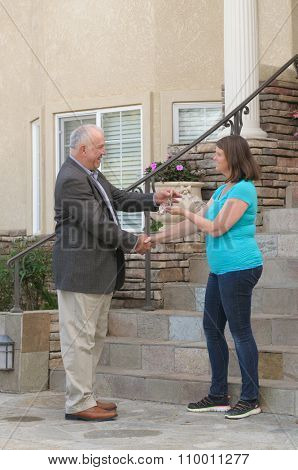 Realtor handing over keys to a house to the new home owner