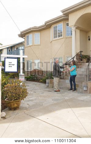 Realtor handing over keys to a house to the new home owner with blank sign with room for your text