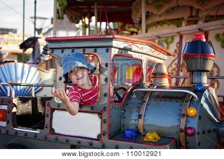 Cute Boy On A Merry-go-round Carousel, Riding A Train