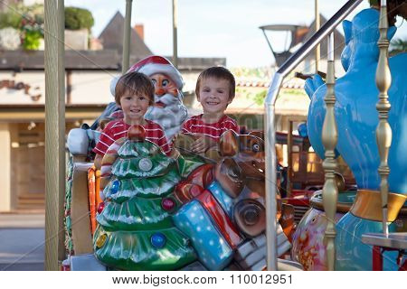 Sweet Boys, Brothers, Riding In A Santa Claus Sledge On A Merry-go-round, Carousel Attraction In Eur