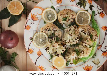 Grilled cauliflower served on a plate with lemon slices as garnish