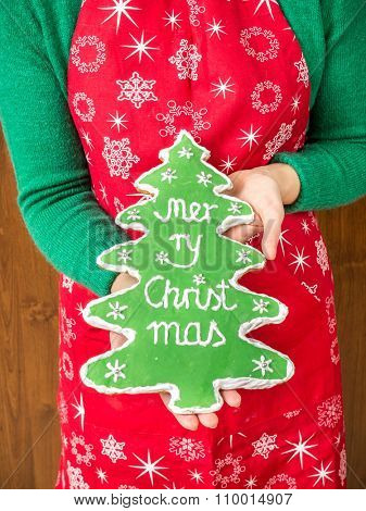Goodwife holding home-made christmas tree-like gingerbread cookie with green icing and Merry Christmas writing