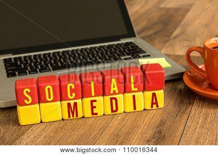 Social Media written on a wooden cube in a office desk