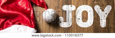 Joy written on wooden with Santa Hat