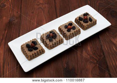 tasty raw vegan dessert on white plate over wood background