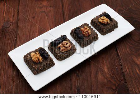 set of raw vegan dessert on white plate over wood background