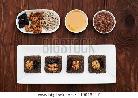 set of raw vegan dessert and ingredients in white plates over wood background