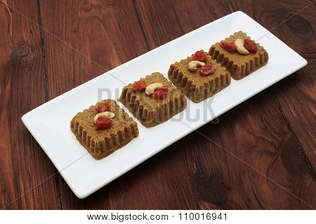 raw vegan halvah on white plate over wood background