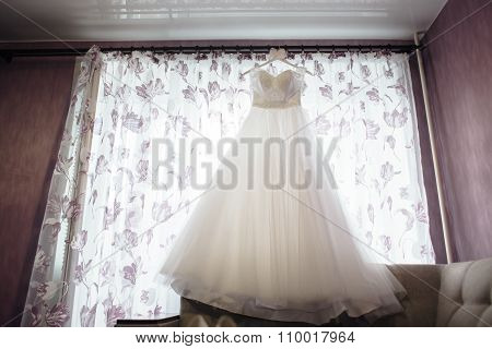 beautiful white wedding dress on hanger on the background of a window