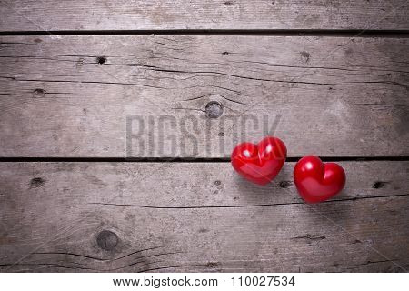 Red Hearts On Aged Wooden Background.