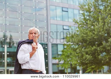 Old business man standing outside of the office in summer