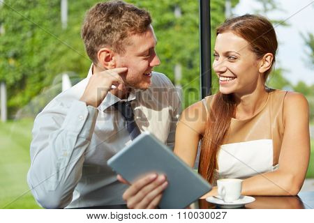 Smiling man and young woman flirting with each other in a coffee shop