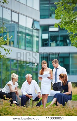 Business team discussing a contract in a meeting outdoors