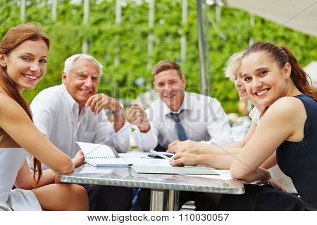 Successful business people sitting outdoors on a table and working