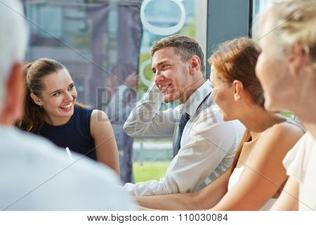 Many business people talking to each other in a team meeting