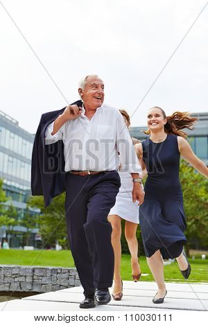 Two business women catching senior manager running away