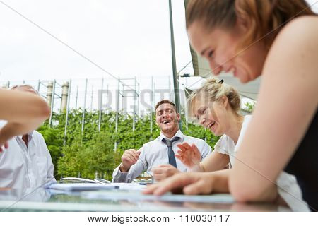 Laughing business people sitting on a table during a meeting outdoors