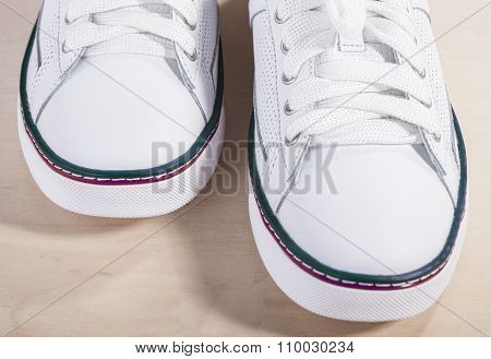 Pair Of White Fashionable Laced Trainers On Wooden Surface