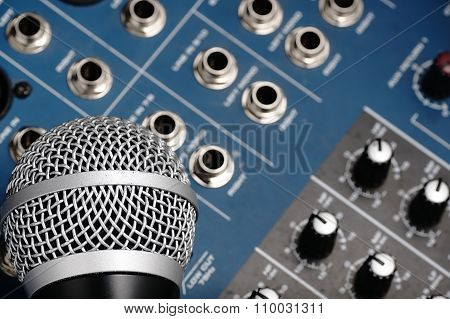 Audio Mixer And A Silver Microphone.