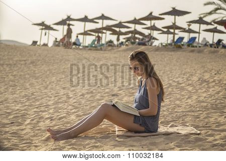 Girl Reads A Book At The Beach