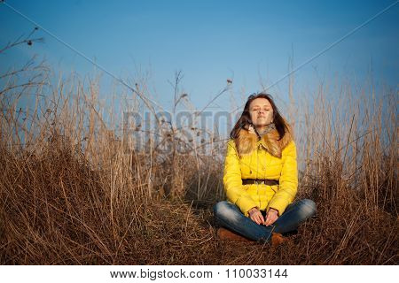 Youn Girl Sitting On Yellow Autumn Grass
