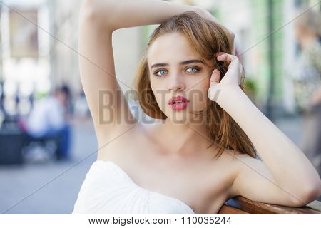 Close up portrait of beautiful model woman in wearing white dress posing summer street