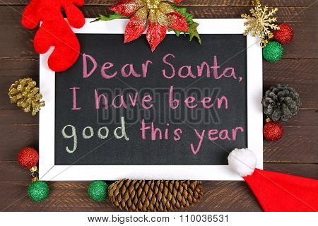A white framed blackboard with a message to Santa Claus, decorated with glittery Christmas decoration on brown wooden background