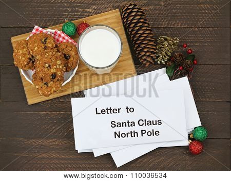 Homemade cookie next to a glass of milk and white envelops with letter to Santa Claus inside on a wooden background