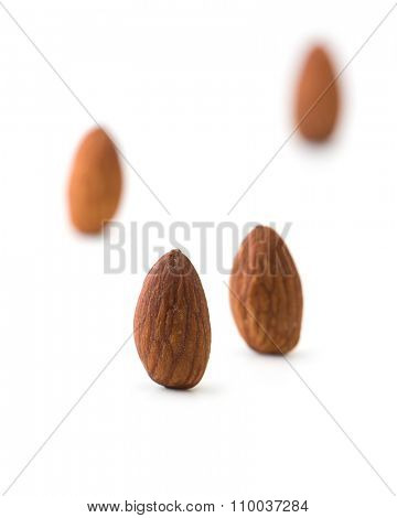 Almonds standing, isolated on white. Four almonds standing with distance between them. Shallow depth of field.